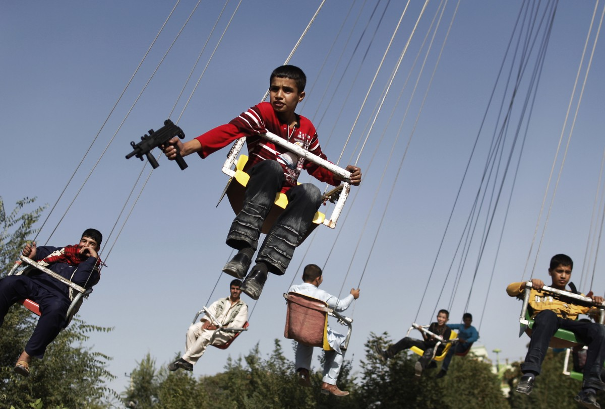 An Afghan boy holds a toy gun as he enjoys a ride with others on a...